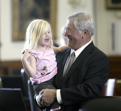 After many long nights working on the state's water management bill, Senator Ken Armbrister is happy to share a moment at his desk with granddaughter Payton.  Payton lives with her mother Holly and father Shane Armbrister, who is a high-school football coach in West Columbia, Texas.