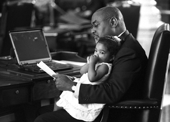 Alena Ellis thinks the whole thing is a bit tiring and rests in her father's lap.  Alena is the youngest  daughter of Senator Rodney Ellis